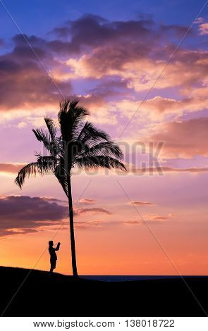 Tropical sunset with silhouettes of photographer and palm tree