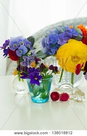 Colorful violets and pancies cut flowers in vases on white desktop