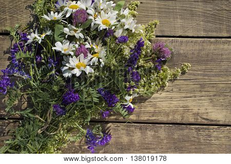 a bouquet of wild flowers, chamomile, clover and weasel on the background of old wooden planks