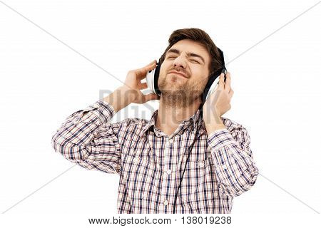 Close-up portrait of a handsome confident blue-eyed dark-haired young man wearing casual plaid shirt singing in head phones with closed eyes. Isolated.