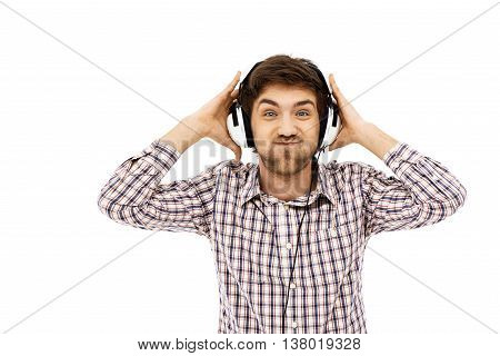 Close-up portrait of handsome funny young blue-eyed dark-haired man wearing casual plaid shirt in head phones. Isolated.
