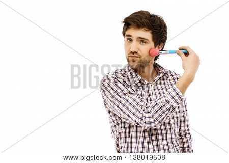 Close-up portrait of handsome young blue-eyed dark-haired man with brush wearing casual plaid shirt. Self make up. Isolated.