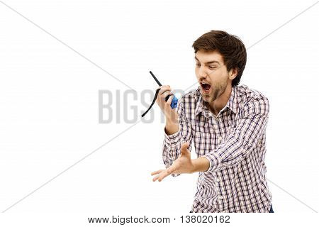 Close-up portrait of handsome angry young blue-eyed dark-haired man screaming in walkie-talkie wearing casual plaid shirt. Isolated.