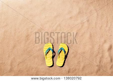 Summer vacation composition with a pair of yellow flip flop sandals on a beach. Sand background, studio shot, flat lay. Copy space.