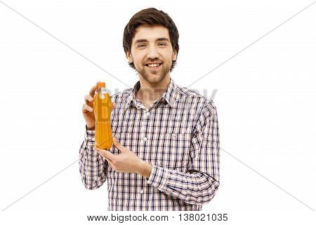 Young handsome cheerful man in plaid shirt showing plastic bottle with orange beverage. Looking at camera. Isolated on white background.