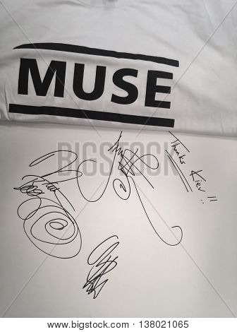Kyiv, Ukraine - July 9, 2016: Autographs of the participants of the musical group Muse: Matt Bellamy, Chris Wolstenholme, Dominic Howard. White T-shirt. Signatures of Muse in a big book.