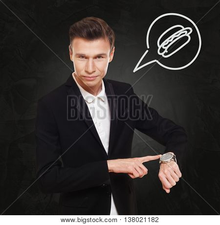 Time to to have lunch. Businessman point at his hand watch showing clock. Man in suit at black background, thinking cloud with hot dog symbol. Lunch break, eating fast food concept