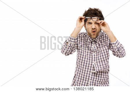 Crazy and funny amused handsome young man in plaid shirt and glasses with messy hair looking at camera. Isolated on white background.