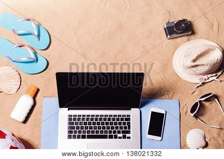 Summer vacation composition with laptop, smart phone, a pair of blue flip flop sandals, hat, sunglasses, sun cream and other stuff on a beach. Sand background, studio shot, flat lay, copy space.