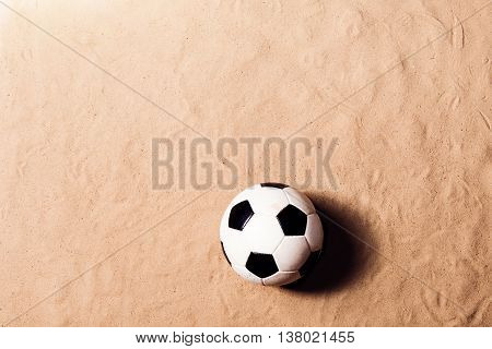 Soccer ball laid on beach. Summer vacation composition. Sand background, studio shot, flat lay. Copy space.