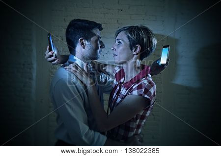 couple of lovers hugging each other in love but in fact looking at the mobile phone over the shoulder in relationship communication problem and internet social network addiction concept