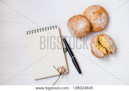 A flat lay of a muffins notebook for records the pen a white background