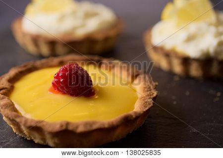 Delicious sweet dessert fresh cheese with lemon and vanilla with raspberry tarts on dark stone slate. Selective focus on lemon slice. Concept of Home baking. Concept of home made desserts.