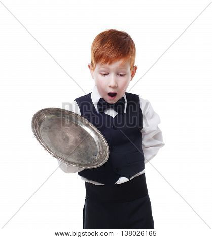Clumsy little waiter drops tray serving something. Redhead child boy in suit shows inattentive waiter failure, isolated at white background