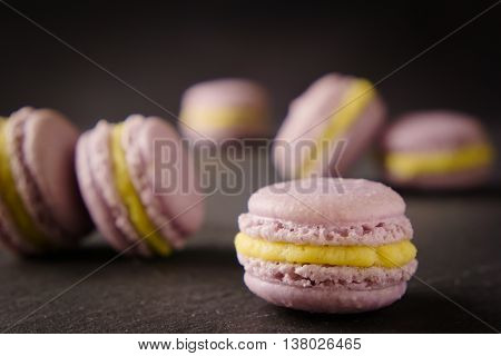 Delicious homemade lavender macaroons with vanilla cream on dark slate. Selective focus on front macaroon.