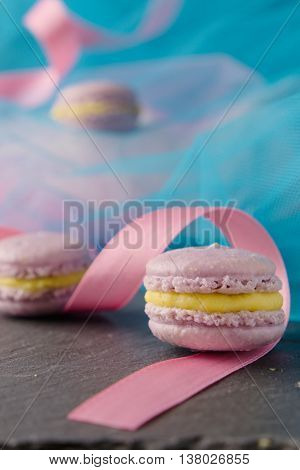 Homemade delicious appetizing sweet lavender macaroons with vanilla creme patissiere in colorful setting with blue teal fabric and pink ribbon