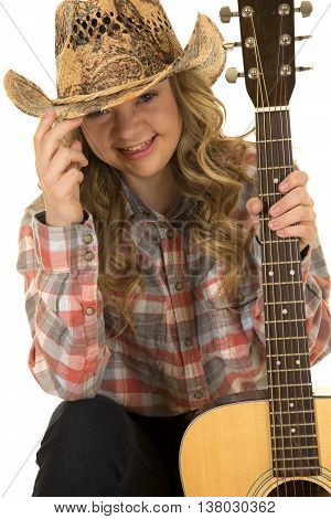 a cowgirl with a big smile holding on to the brim of her hat with her guitar in her hands.