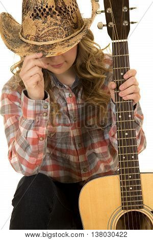 a cowgirl hiding her face holding onto her guitar.