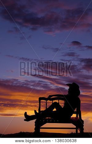 a silhouette of a cowgirl sitting on a bench with a beautiful sunset in the sky.