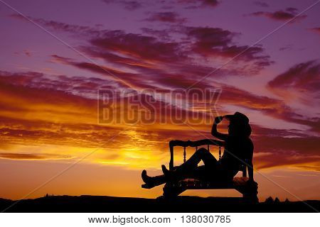 a silhouette of a cowgirl sitting on a bench with a beautiful sky behind her.