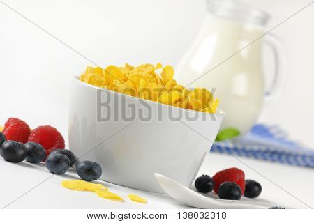 bowl of corn flakes and jug of milk on checkered dishtowel - close up
