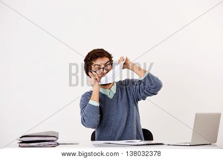 Handsome young businessman in glasses sitting at the office desk having fun with papers. Looking at camera. Isolated on white background.