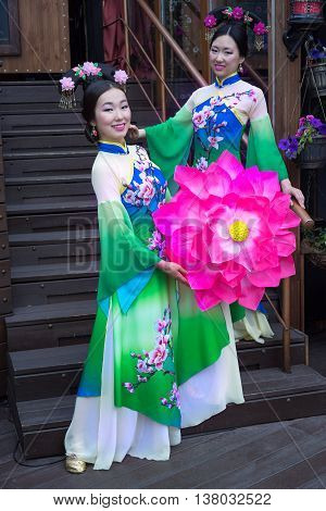 Two Asian girls in traditional Chinese dresses with umbrella in the form of lotus flowers standing on the staircase