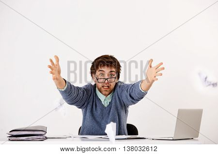 Handsome young businessman in glasses sitting at the office desk screaming and throwing papers forward to camera. Looking at camera. Isolated on white background.