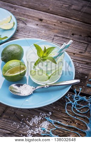 Light refreshing drink with slices of cucumber, lime, ice cubes and mint on a wooden background in a glass beaker low