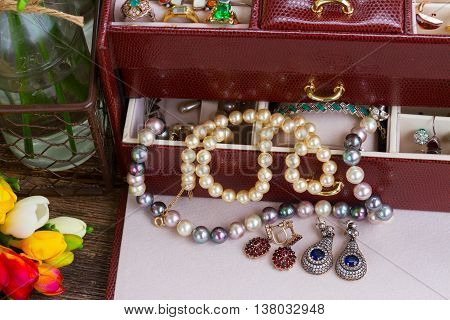 Jewellery in treasure box with fresh fresia flowers on desktop