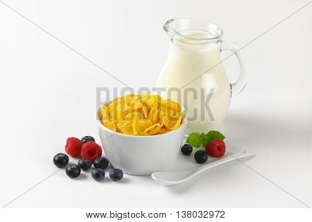 bowl of corn flakes and jug of milk on white background