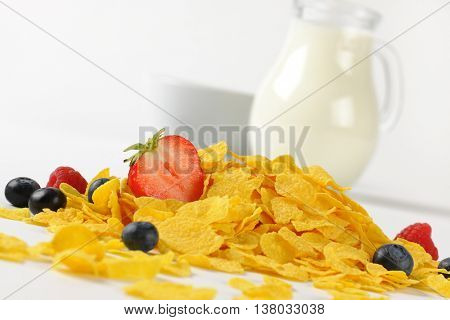 jug of milk and corn flakes with berry fruits on white background - close up
