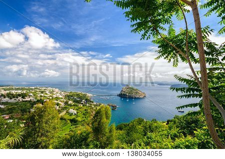 Aerial view on Aragonese castle through green oliage Ischia Italy