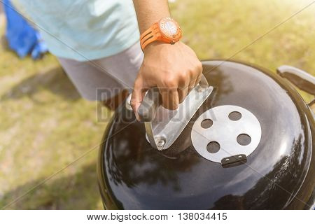 Close up of male hand opening cover of black grill. Man is standing on grass
