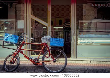 Old bicycle standing in front of a bakery