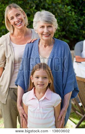 Grandmother with her daughter and grand daughter looking at the camera in the garden