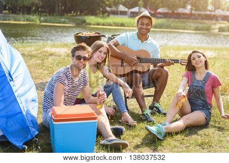 Joyful young friends are relaxing in the nature. They are sitting on grass and looking at camera with happiness. Man is playing guitar and smiling
