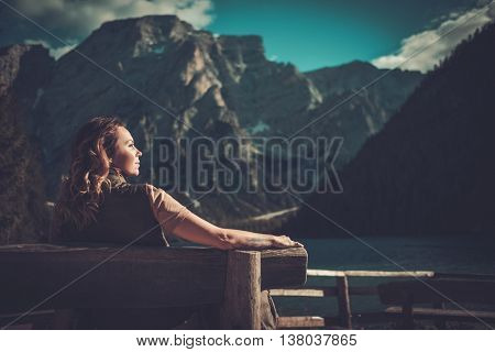 Woman enjoying amazing view of Lago di Braies with mountain forest on the background.