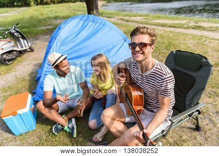 Cheerful friends are relaxing near river. They are talking and laughing. Man is playing guitar and looking at camera happily
