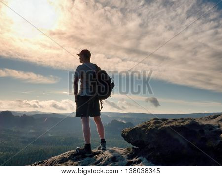 Alone Tourist With Sporty Backpack Stand On Cliff Edge And Watching Into Deep Valley Bellow.