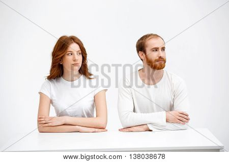 Beautiful redhead girl and boy sitting at the white table. Isolated at the white background. Look aside.