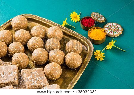 sesame laddu or tulgul or til gul laddu or ladu served in brass plate, favourite sweet dish in Makar Sankranti Festival in India, indian festival sweets, huldi kumkum with flowers, kite festival