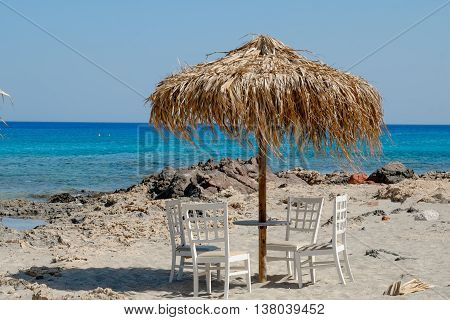 White Chairs And Table With View Of Tropical Turquoise Ocean Under A Straw Umbrella