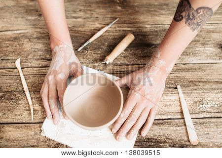 Pottery molding on wooden table top view. Artisan hands with clay bowl and special tools flat lay , creativity in arts