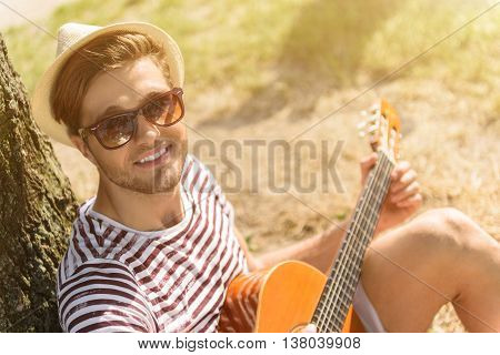 Carefree young man is enjoying music in nature. He is sitting near tree and holding guitar. Guitarist is looking at camera and smiling