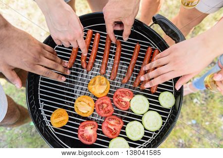 Close up of human hands. Men and women taking roasted sausages and vegetables from grill