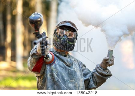 Cool guy with paintball gun and smoke grenade