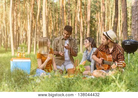 Happy men and women are talking and laughing in the nature. They are sitting on grass. Man is playing guitar with enjoyment