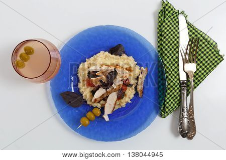 Traditional italian risotto with chicken tomato basil and parmesan on blue plate with knife and fork on napkin and glass of wine against white background horizontal top view