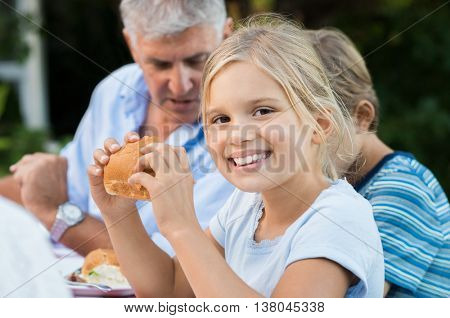 Young pretty girl enjoying eating bread and looking at camera. Little cute girl eating sandwich with brother and grandfather. Portrait of a young girl having lunch with family on picnic.